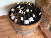 Photo of half wine barrel filled with bottles of wine