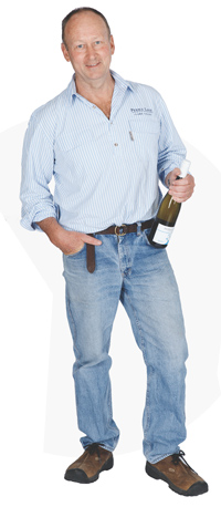 Photo of Peter Treloar holding a bottle of Penna Lane Riesling